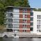 Betongkonstruksjon med trekledning i stående og liggende panel på Kopervik Brygge