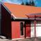 Moderne driftsbygning med stående vindu i gavl, overbygg med PVC- plater og teglstein