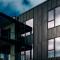 Sorte fasadeplater i kontrast til hvit trekledning - Rossabø Havn leilighetskompleks