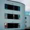 Kurvet trekledning og innfelte sorte vinduspartier på Rossabø Havn - Arkitektkontoret Brekke Helgeland Brekke AS