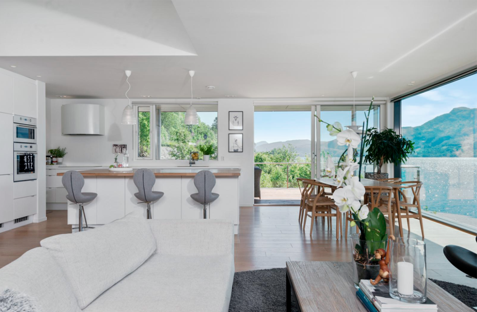 Hvite gipsvegger danner ramme rundt utsikten i boligen i Sandeid tegnet av Arkitektkontoret Brekke Helgeland Brekke AS