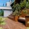 Opparbeidet uteområde med tredekke, betong og grønne planter gir privatliv og en intim sfære på den bratte tomta